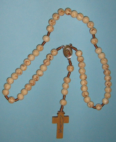 Rosary - E8145030 WH - Wooden Rosary - white - Rosary of Immaculate Mary (Gospa) of Medjugorje (Međugorje). These wooden white beads rosaries - chaplet are handmade in Medjugorje, Bosnia and Herzegovina. Because they are handmade, each is different. The white color and shape will be different on every rosary. These rosaries are not blessed. A great gift for new car owner's used on rear view mirror (car). These wood rosaries are handmade by a family that suffered death and destruction of their home during the war in 1991-1994. These rosaries are their only means of income. Chaplet - Rosary Features: 9 mm oval white wooden Catholic beads (with signs of crosses) on a Rope for Praying the Rosary, and a cca. 3 x 4,5 cm wood cross. White Wooden Beads with a 2 sided Center (with Miracle Photo of the Virgin Mary – Lady of Peace). Natural wood rosary mounted on a string. Length: cca. 50 + 10 cm. See picture on millimeter paper. Items can vary slightly from the picture.