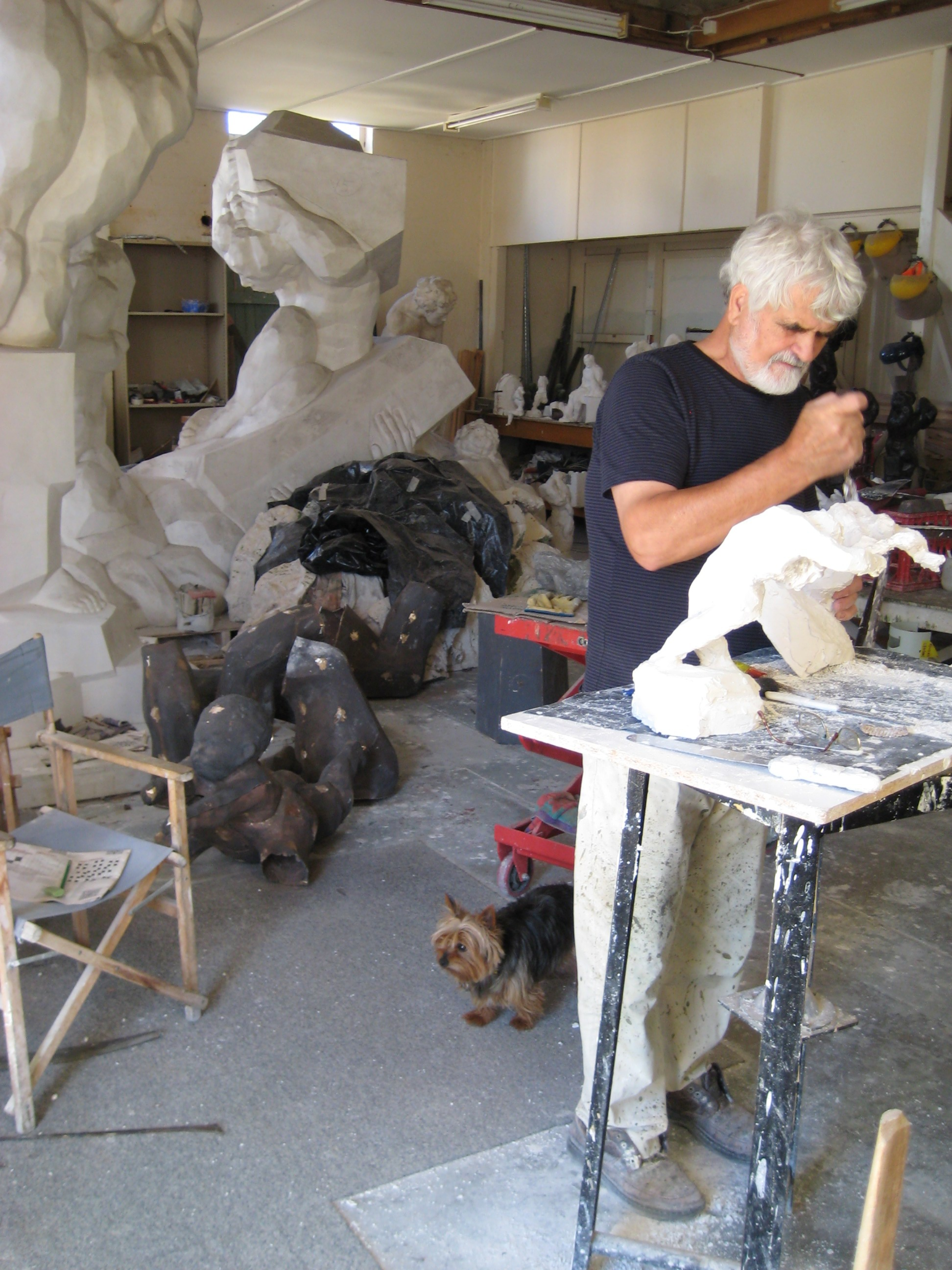 ANTE DABRO ANTE DABRO AT WORK IN HIS WORKSHOP STUDIO AT EN:CANBERRA INTERNATIONAL AIRPORT. BEHIND ARE THE FULL SIZED MODELS FOR GENESIS AT LEFT AND RESILIENCE; ON THE FLOOR ARE THE UNASSEMBLED PARTS IN CAST BRASS FOR MOTHER AND CHILD. AT DABRO'S FEET IS HIS AUSTRALIAN SILKY TERRIER, CHIKO.