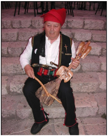 "GUSLE - CROATIAN FOLK INSTRUMENT CROATIAN ANTE MINSTREL BIOČIĆ FROM IMOTSKI. APPEARANCE ON ""IMOTSKI SILIMA"" 6 JULY 2002. PROWESS, CROATIAN IDENTITY, DIGNITY AND CATHOLICISM WERE THE BASIC TAGS AND DWELT CROATIAN MINSTREL. THIS IS CLEARLY SEEN IN THE ACCOMPANYING FIGURE WHICH SHOWS THE MINSTREL ANTE BIOCIC. HERE WE SEE THE HOLSTER AND BELT JATAGAN FOR ANTIN, THERE ARE FIDDLE MAPLE, THERE IS ALSO A CRUCIFIX ON THE COSTUMES AND CROWNS AROUND THEIR NECKS."